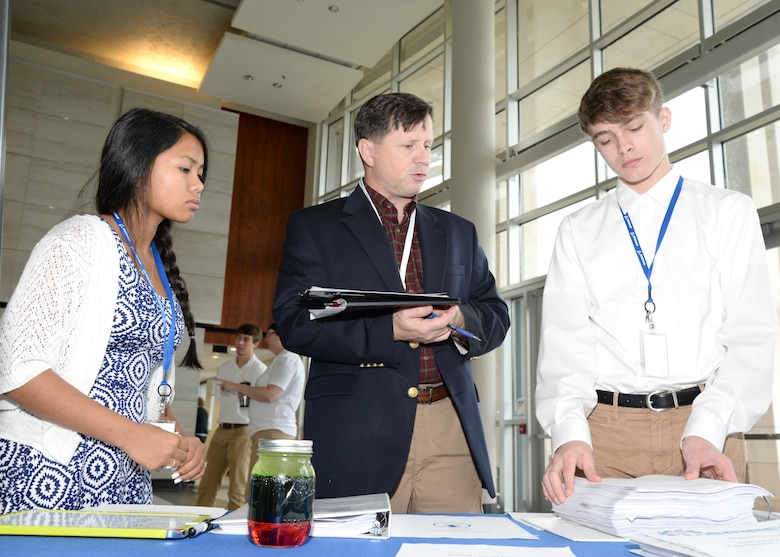 Russ Dunford, U.S. Army Engineering and Support Center, Huntsville chief of operations, speaks to McCoy Floyd, left, and Zachery Amerson, Palmetto Scholars Academy, North Charleston, South Carolina, about their conceptual payload during the InSPIRESS event at UA Huntsville, Dec. 11.