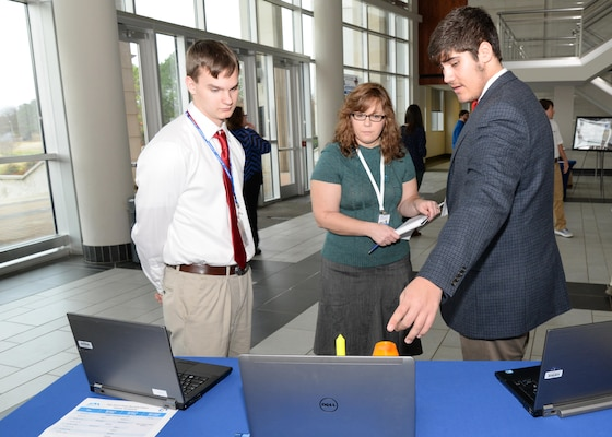 Betina Johsnon, U.S. Army Engineering and Support Center, Huntsville Ordnance and Explosives Design Center chief, speaks to Sebastian Stewart, left, and Liam Bair, Hartselle High School, Hartselle, Alabama, about their conceptual payload during the InSPIRESS event at UA Huntsville, Dec. 11.