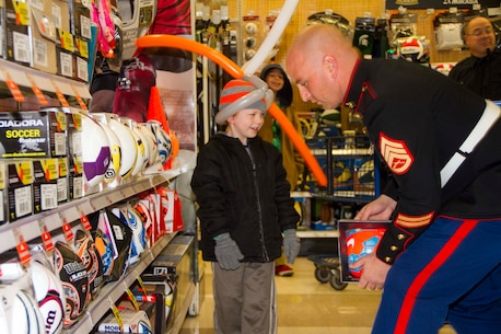 Staff Sgt. Benjamin Dittenbir, Recruiting Station Lansing, Recruiting Sub-Station Central Michigan staff noncommissioned officer-in-charge, helps Timothy Laskowski pick out a toy at Meijer's Shop with the Heroes event in Mt. Pleasant, Mich., Dec. 8, 2015. Meijer selected a group of underprivileged kids and granted them a 100 dollar spending allowance so they could get their family members gifts, and maybe something for themselves too. They also had volunteers to help them wrap the gifts, provided pizza, drinks and a DJ for the kids and their families to enjoy.