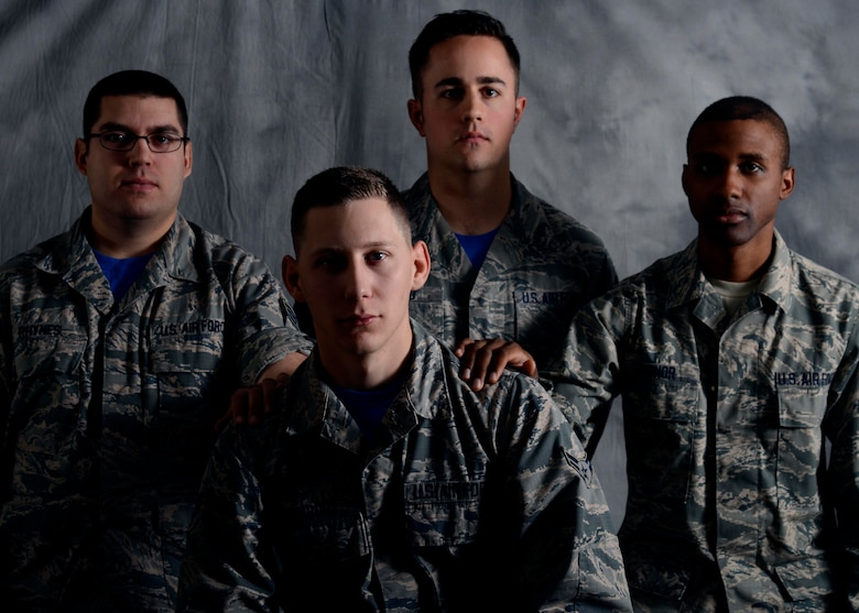 Three 22nd Air Refueling Wing Public Affairs Airmen reach out to Airman 1st Class Christopher Thornbury, front-center, Dec. 11, 2015, at McConnell Air Force Base, Kan. Thornbury says his Air Force family has been with him for over a year and helped him through the loss of his son, Emmitt Alan Thornbury. (U.S. Air Force photo/Senior Airman Colby Hardin)