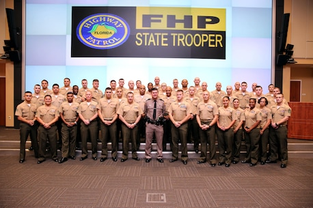 The Marines of U.S. Marine Corps Forces, South pose for a photograph with Trooper Jose Sanchez, Troop E, Florida Highway Patrol, after a vehicle safety brief Dec. 11, 2015.  Trooper Sanchez, a 28-year veteran of the FHP, volunteered to give the Marines the safety brief prior to the holiday break.  (Official Marine Corps photo by SSgt. Earnest J. Barnes/Released)