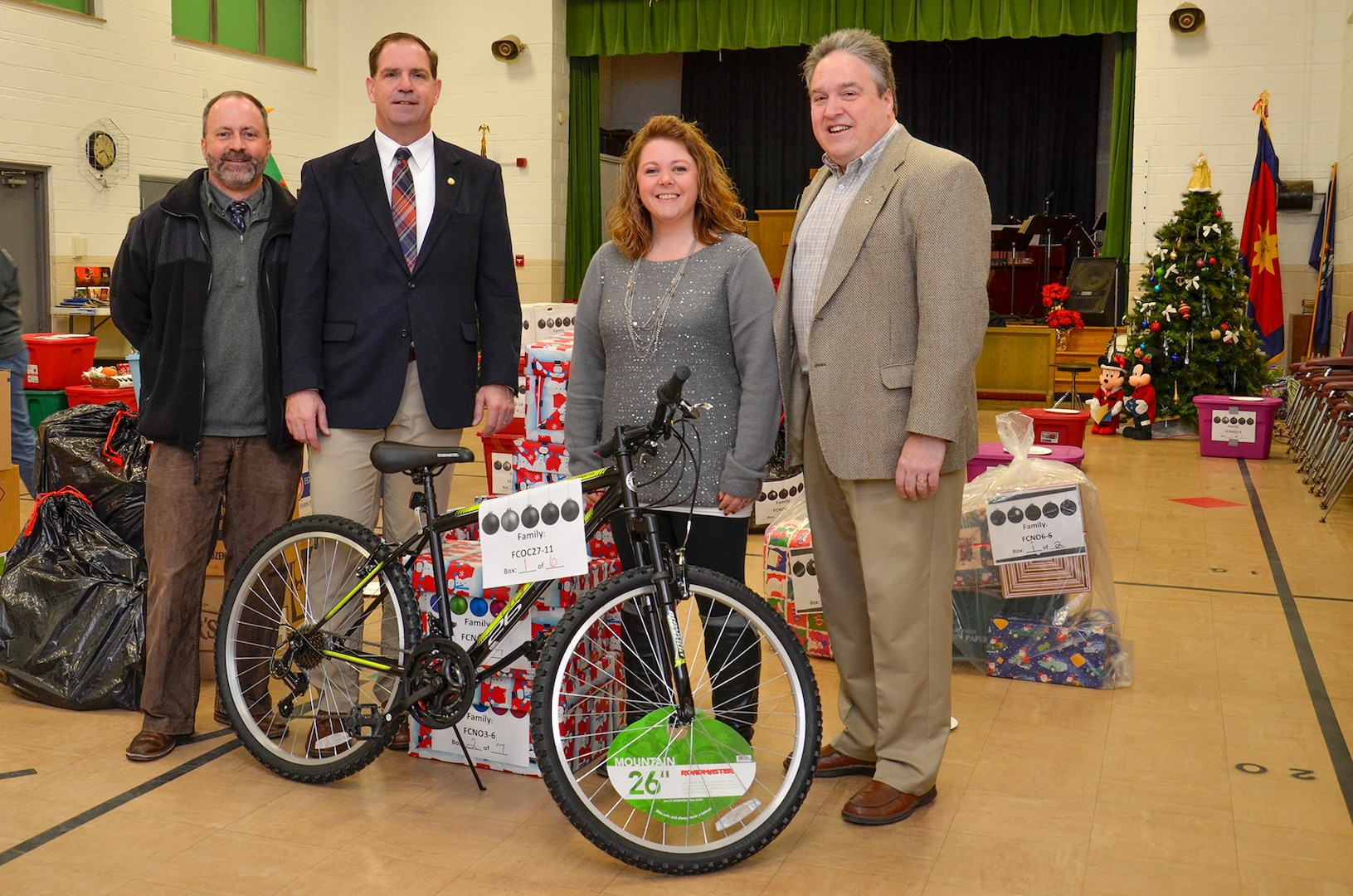 Don Phillips (left), DLA Installation Support at Battle Creek's acting site director, and DLA Disposition Services Director Mike Cannon (left center) and Logistics Information Services Director Ray Zingaretti join Tiffany Schmidt, a DLA marketing specialist and the DLA coordinator for the Adopt a Family campaign, as agency employees help the Salvation Army distribute the food and items collected.