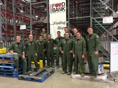 Members of 435th Flying Training Squadron class 16-DBR from Joint Base San Antonio-Randolph take a break after packing 49,875 pounds of food on 95 pallets for distribution to the local community in the form of 39,900 meals to 3,325 local families while at the San Antonio Food Bank Dec. 12, 2015.  The community outreach project, part of the unit's Wingman Day, broke the single-day record for food packed at the food bank. (U.S. Air Force courtesy photo)