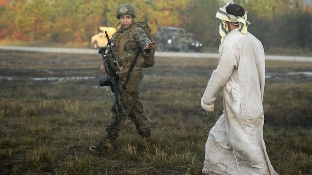 A team leader with 2nd Air Naval Gunfire Liaison Company, II Marine Headquarters Group, motions to a role player at Marine Corps Base Camp Lejeune, N.C., during a Security Assistance Liaison Team training exercise to improve their ability to work with coalition forces, Dec. 10, 2015. The Security Assistance Liaison Team will support Operation Resolute Support in Afghanistan under the authority of United Nations Security Council Resolution 2189.