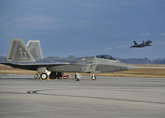 An F-22 Raptor from Tyndall Air Force Base, Fla., sits on the flightline while a Raptor launches from the Tyndall runway Dec. 10, 2015, during Checkered Flag 16-1. The week-and-a-half long exercise focuses on the involvement of the F-22 Raptor, F-35A Lightning II's and legacy aircraft training in a large-force exercise to enhance combat airpower capabilities. (U.S. Air Force photo/Senior Airman Sergio A. Gamboa)