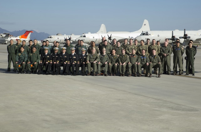 Members of the Japan Maritime Self-Defense Force Air Reconnaissance Squadron VQ-81 and Fleet Air Reconnaissance Squadron VQ-1 pose for a group picture at Marine Corps Air Station Iwakuni, Japan, Dec. 8, 2015. VQ-1 came to MCAS Iwakuni for an annual unit exchange between VQ-1 and VQ-81. The two units discussed their plans to increase their unit interoperability, strengthening the bond between the two units.