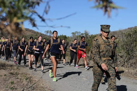 Commanding Officer of Recruiting Station Los Angeles, Maj. Aixa Dones, leads Marine enlistees of RSLA on a two-mile hike during a pool function at Weapons Field Training Battalion, Marine Corps Base Camp Pendleton, Calif., Dec. 12, 2015. During the event, recruiters teamed with drill instructors to mentally and physically prepare enlistees from Los Angeles, San Diego and Orange County for boot camp and taught classes about military appearance and Marine Corps history. (U.S. Marine Corps photo by Staff Sgt. Alicia R. Leaders/Released)