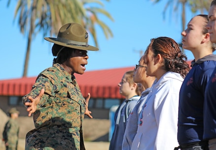 Drill Instructor Staff Sgt. Maria S. Zalwango, corrects a Marine enlistee during a pool function at Weapons Field Training Battalion, Marine Corps Base Camp Pendleton, Calif., Dec. 12, 2015. During the event, recruiters teamed with drill instructors to mentally and physically prepare enlistees from Los Angeles, San Diego and Orange County for boot camp and taught classes about military appearance and Marine Corps history. (U.S. Marine Corps photo by Staff Sgt. Alicia R. Leaders/Released)