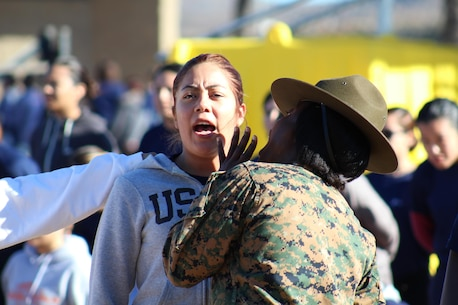 A Marine enlistee responds to Drill Instructor Staff Sgt. Maria S. Zalwango's corrections during a pool function at Edson Range, Marine Corps Base Camp Pendleton, Calif., Dec. 12, 2015. During the event, recruiters teamed with drill instructors to mentally and physically prepare enlistees from Los Angeles, San Diego and Orange County for boot camp and taught classes about military appearance and Marine Corps history. (U.S. Marine Corps photo by Staff Sgt. Alicia R. Leaders/Released)