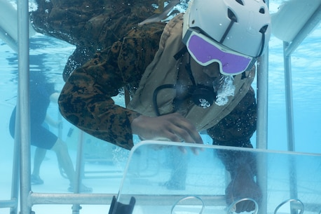 Lance Cpl. Carl King escapes the Shallow Water Egress Training chair blindfolded on Nov. 17, 2015, on Camp Hansen, Okinawa, Japan. King, along with other Marines from the 31st Marine Expeditionary Unit, participated in the pre-deployment training which allows MEU Marines to prepare for real-life situations. King, from Albany, Ga., is a public affairs Marine with the 31st MEU. (U.S. Marine Corps photo by Cpl. Thor Larson/Released)