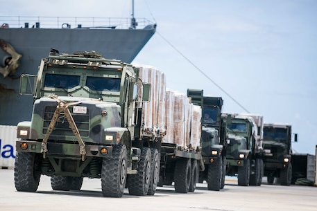 U.S. Marine 7-ton trucks with Combat Logistics Battalion 31, 31st Marine Expeditionary Unit, prepare to distribute water and supplies from the USS Ashland (LSD 48) to local civilians as part of typhoon relief efforts in Saipan, Aug. 11, 2015. The 31st MEU and the ships of the Bonhomme Richard Amphibious Ready Group are assisting the Federal Emergency Management Agency with distributing emergency relief supplies to Saipan after the island was struck by Typhoon Soudelor Aug. 2-3. (U.S. Marine Corps photo by Lance Cpl. Brian Bekkala/Released)