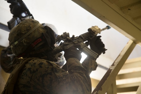 Lance Cpl. Alexis Vergara clears a stairway before his fire team moves to the second floor in a building in Central Training Area's Combat Town in Okinawa, Japan, Nov. 6 2015. The Marines with Combat Logistic Battalion 31, 31st Marine Expeditionary Unit, used special effect small-arms marking system rounds and cleared buildings with opposing forces during a three day training event. Vergara, a native of Chino Hills, California, is a military policeman with Military Police Detachment, CLB 31, 31st MEU. (U.S. Marine Corps photo by Cpl. Abbey Perria/Released)