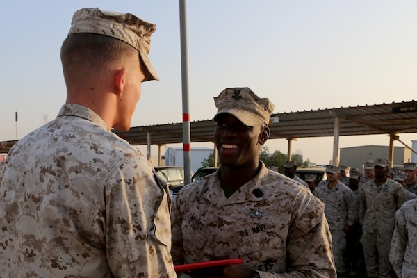 U.S. Navy Petty Officer 2nd Class Ambrose McGill, a hospital corpsman with Special Purpose Marine Air Ground Task Force—Crisis Response—Central Command, is presented his Fleet Marine Force pin during a recognition ceremony at an undisclosed location in Southwest Asia, Dec. 12, 2015. McGill spent countless hours studying Marine Corps knowledge that Marines would receive during boot camp in order to earn the pin. (U.S. Marine Corps photo by Sgt. Owen Kimbrel/RELEASED)