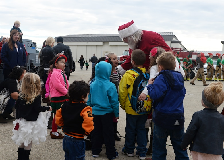 Children of Team Beale surround Santa Clause during the annual Children's Holiday Party Dec. 12, 2015, at Beale Air Force Base, California. Thousands of presents were donated by multiple suppliers and were handed out to the children of Team Beale. In addition, the event included photos with Santa Clause and his elves, a raffle and various holiday activities. (U.S. Air Force photo by Airman 1st Class Ramon A. Adelan)
