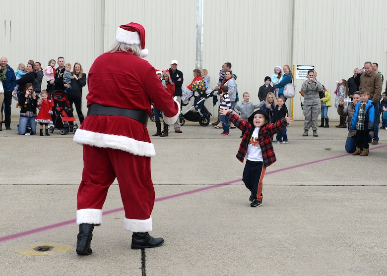 A child of Team Beale runs to Santa Clause during the annual Children's Holiday Party Dec. 12, 2015, at Beale Air Force Base, California. Thousands of presents were donated by multiple suppliers and were handed out to the children of Team Beale. In addition, the event included photos with Santa Clause and his elves, a raffle and various holiday activities. (U.S. Air Force photo by Airman 1st Class Ramon A. Adelan)