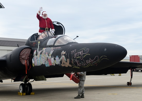 Santa Clause emerges from a U-2 Dragon Lady during the annual Children's Holiday Party Dec. 12, 2015, at Beale Air Force Base, California. Thousands of presents were donated by multiple suppliers and were handed out to the children of Team Beale. In addition, the event included photos with Santa Clause and his elves, a raffle and various holiday activities. (U.S. Air Force photo by Airman 1st Class Ramon A. Adelan)