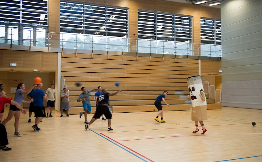 Airmen pummel a cigarette mascot with dodgeballs to warm up for the RUFit Dodgeball Tournament in the fitness center Dec. 11, 2015, at Spangdahlem Air Base, Germany. Information booths from the four pillars of RUFit, social, mental, spiritual and physical, were set up to provide information to the players during the games. (U.S. Air Force photo by Staff Sgt. Christopher Ruano/Released)