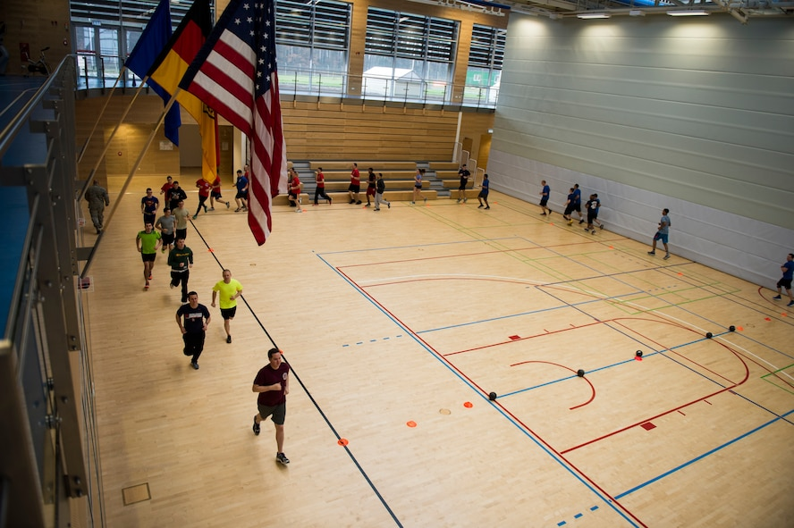 Airmen run around the court to warm up for the RUFit Dodgeball Tournament in the fitness center Dec. 11, 2015, at Spangdahlem Air Base, Germany. Warm-ups consisted of multiple cardio routines followed by arm and leg stretches before the game began. (U.S. Air Force photo by Staff Sgt. Christopher Ruano/Released)