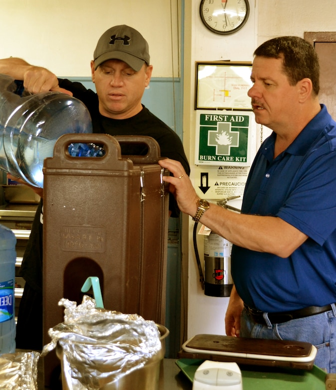 Capt. Daniel Taylor, left, a logistics readiness officer with the 111th Attack Wing, and Chief Master Sgt. James Finn, the superintendent of the 111th Security Forces Squadron, make iced tea for a holiday party held for severely-disabled adults in the dining facility at Horsham Air Guard Station, Pennsylvania, Dec. 13, 2015. The guests were presented with food, music, gifts and a visit by Santa Claus during the annual event.  (U.S. Air National Guard photo by Tech. Sgt. Andria Allmond/Released)