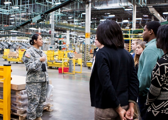 Students from Central York High School talk about real-world logistics inside the Eastern Distribution Center at DLA Distribution Susquehanna, Pa., with Army Chief Warrant Officer 4 Brenda Johnson on Dec. 10.