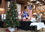 Bensley Elementary School 5th graders, Angela Bernardina Marinex and Andersson Revelo Castro, along with Defense Logistics Agency Aviation Commander Air Force Brig. Gen. Allan Day throw the switch to light the tree during the annual Tree Lighting Ceremony Dec. 10, 2015 in the Frank B. Lotts Conference Center on Defense Supply Center Richmond, Virginia.