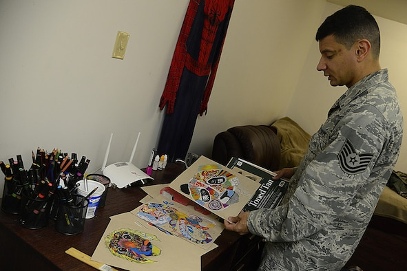 Air Force Tech. Sgt. Juan Hernandez, 731st Air Mobility Squadron air terminal operations center senior information controller, shows some of his artwork on Osan Air Base, South Korea, Dec. 3, 2015. Hernandez is partially colorblind, so he taught himself to identify multiple shades of colors using their assigned numbers. U.S. Air Force photo by Senior Airman Kristin High
