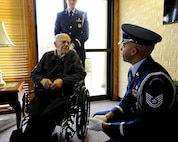 Roy Mullinax, a World War II Army veteran, speaks with Tech. Sgt. Terrance Williams, the 22nd Air Refueling Wing Honor Guard NCO in charge, during a recognition ceremony Dec. 8, 2015, in Newton, Kan. Mullinax enlisted in the Air Force shortly after the end of World War II, and his years of military service led to his recognition with a veteran's pin through his hospice center. (U.S. Air Force photo/Senior Airman Victor J. Caputo)