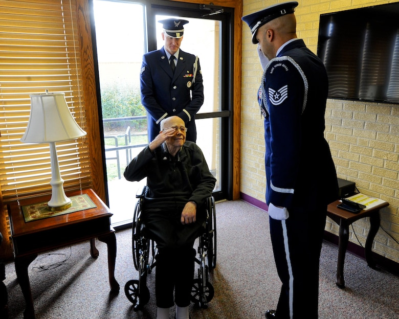Roy Mullinax, a former Airman, returns a salute to Tech. Sgt. Terrance Williams, the 22nd Air Refueling Wing Honor Guard NCO in charge, after being presented with a veteran's pin during a recognition ceremony Dec. 8, 2015, in Newton, Kan. Members of the 22nd ARW Honor Guard recognized Mullinax for his years of service during a special ceremony at the request of his family. (U.S. Air Force photo/Senior Airman Victor J. Caputo)