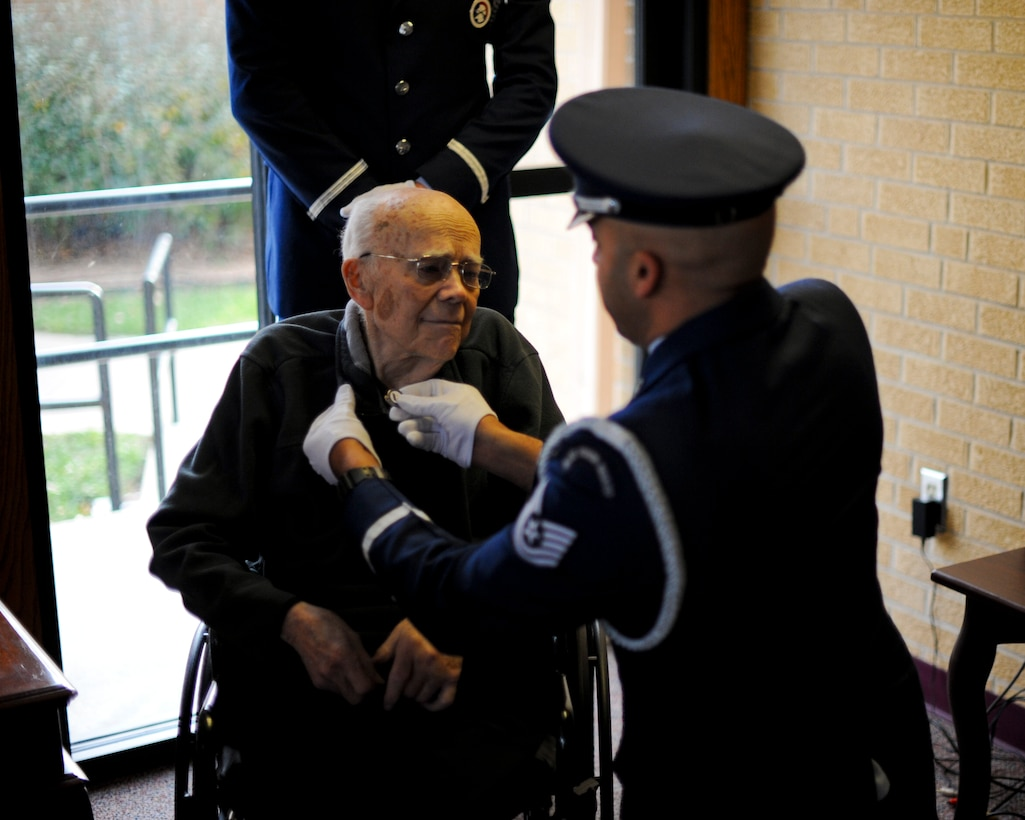 Tech. Sgt. Terrance Williams, the 22nd Air Refueling Wing Honor Guard NCO in charge, places a veteran's pin on the collar of Roy Mullinax, a World War II veteran, Dec. 8, 2015, in Newton, Kan. Mullinax enlisted in the Army toward the end of WWII before joining the Air Force and working for the federal government for more than 50 years before his retirement in 2004. (U.S. Air Force photo/Senior Airman Victor J. Caputo)