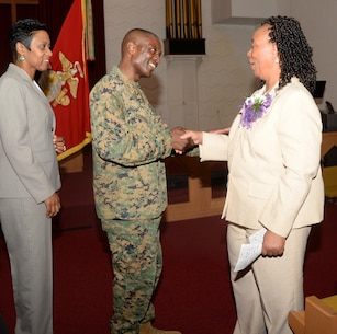 Col. James C. Carroll III, commanding officer, Marine Corps Logistics Base Albany, congratulates Virginia Williams, IT supervisor, MCLB Albany, during her retirement ceremony, Dec. 10, in the base's Chapel of the Good Shepherd.