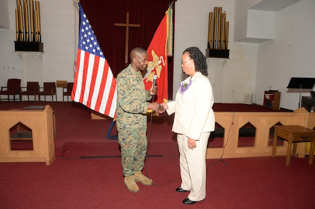 Col. James C. Carroll III, commanding officer, Marine Corps Logistics Base Albany, presents Virginia Williams, IT supervisor, MCLB Albany, with a command coin during her retirement ceremony, Dec. 10, in the base's Chapel of the Good Shepherd.