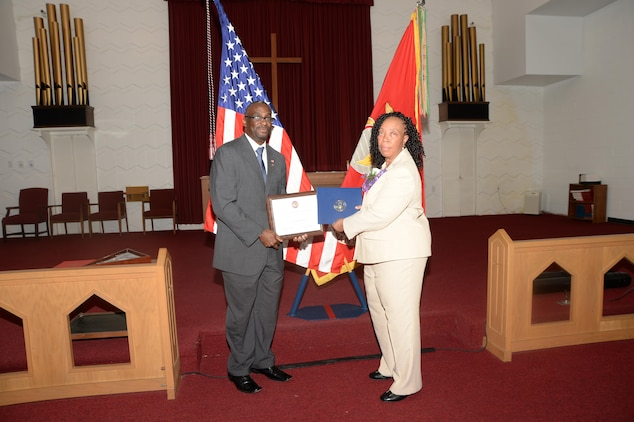 Virginia Williams, IT supervisor, Marine Corps Logistics Base Albany, receives a letter of commendation from Kenneth J. Cutts on behalf of Congressman Sanford D. Bishop Jr., Dec. 10, during her retirement ceremony in the base's Chapel of the Good Shepherd.