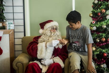 Santa Claus listens to what children want for Christmas and then gives out candy canes during the event, Santa's Little Helper, on Camp Hansen, Okinawa, Japan, Dec. 12, 2015. The event also had Santa fast rope out of a helicopter, fake snow, a bouncy castle, face painting and food served. The event was hosted by Combat Assault Battalion, 3rd Marine Division, III Marine Expeditionary Force and Marine Corps Community Services. (U.S. Marine Corps photo by Cpl. Tyler S. Giguere/Released)