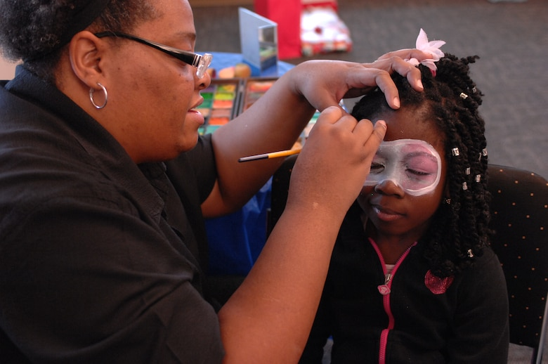 A child attending a holiday party sponsored by the Reconnaissance Crews Booster Club squints as her face is painted at the Pointe at Rising View, Offutt Air Force Base, Neb., Dec. 12, 2015. The event combined a holiday party with a shopping trip in which underprivileged children received money to spend on winter clothing and shoes. (U.S. Air Force photo/Senior Airman Rachel Hammes)