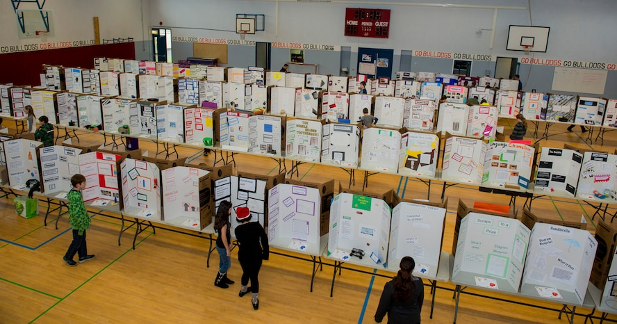 Spangdahlem Middle High School students and faculty members view multiple display boards inside the SMHS gymnasium during the Invention Convention at Spangdahlem Air Base, Germany, Dec. 15, 2015. More than 100 students participated in the convention. (U.S. Air Force photo by Airman 1st Class Luke Kitterman/Released)
