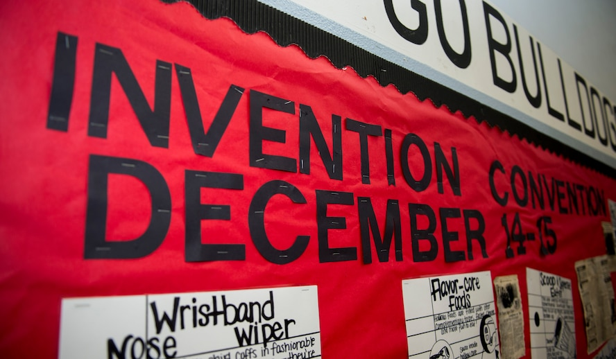 An Invention Convention sign is displayed on the wall of the gymnasium at Spangdahlem Middle High School at Spangdahlem Air Base, Germany, Dec. 15, 2015. The convention is a two-day event where students from the fifth to the eighth grades display their inventions to the base community. (U.S. Air Force photo by Airman 1st Class Luke Kitterman/Released)