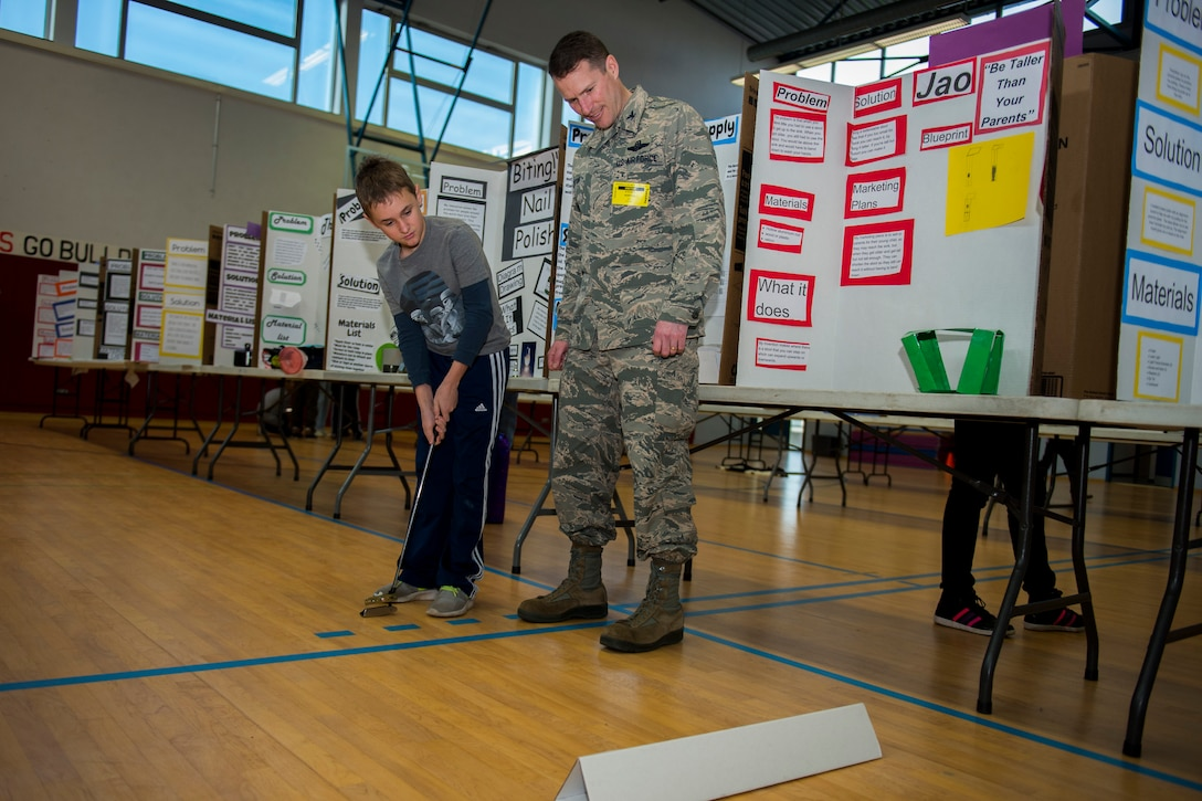 """A student shows his invention of a """"laser putter"""" to U.S. Air Force Col. Steve Horton, 52nd Fighter Wing vice commander, during the Invention Convention at Spangdahlem Middle High School at Spangdahlem Air Base, Germany, Dec. 15, 2015. The students explained and demonstrated their inventions to Horton and a board of judges. (U.S. Air Force photo by Airman 1st Class Luke Kitterman/Released)"""