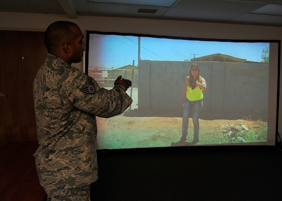 Staff Sgt. Jeffrey Johnson-Dean, 30th Security Forces Squadron unit trainer, aims a training taser at a virtual simulation Dec. 14, 2015, Vandenberg Air Force Base. VirTra, a use-of-force simulator, prepares Airmen for the most difficult real-world situations, and builds situational awareness during extreme stress. (U.S. Air Force photo by Senior Airman Kyla Gifford/ Released)