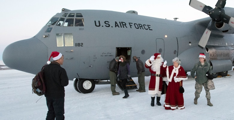 ST. MARY'S, Alaska -- Santa Claus and Mrs. Claus wave as they exit an Alaska Air National Guard C-130 here Dec. 5, 2015. The Clauses were here as part of Operation Santa Claus, a nonprofit organization partnered with the Alaska National Guard to collect toys, school supplies and food staples and deliver them to school children in Alaska's remote  communities. This mission was the second and final Op Santa mission of 2015. St. Mary's was the site of the original Operation Santa Claus in 1957. (U.S. Air National Guard photo by Capt. John Callahan/ Released)