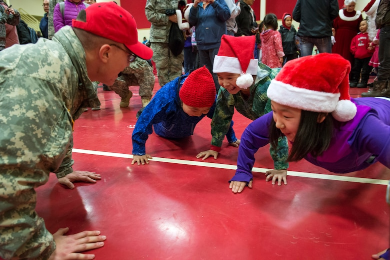 Alaska Army National Guard Spc. Michael Notti does pushups with elementary school children at St. Mary's, Alaska, during Operation Santa Claus, Dec. 5, 2015. This year marks the 59th year of the program, during which volunteers from approximately 30 groups and organizations came together to bring holiday cheer to underserved, remote communities across Alaska. (U.S. Air Force photo/Alejandro Pena)