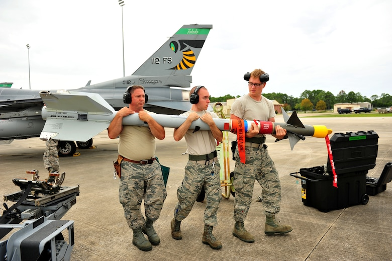 Master Sgt. David Mills, Staff Sgt. Tom Burden and Senior Airman Anthony Vance, weapons loaders from the 180th Fighter Wing, Ohio Air National Guard, transport an Air Intercept Missile, commonly referred to as an AIM9 or sidewinder, to be loaded on an F-16 Fighting Falcon September 15, at Tyndall Air Force Base, Florida. About 120 Airmen from the 180th FW traveled to Tyndall to participate in the Combat Archer exercise, a weapons system evaluation program designed to test the effectiveness of our Airmen and air-to-air weapon system capability of our F-16s and other combat aircraft. Training allows our pilots to provide a vital link for the defense of our country. Air National Guard photo by Senior Master Sgt. Beth Holliker/Released