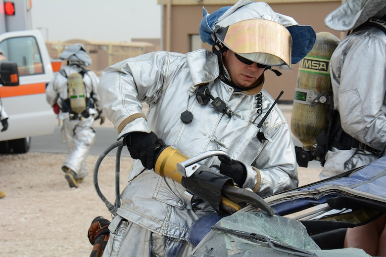 A 379th Expeditionary Civil Engineer Squadron firefighter uses the Jaws of Life to take the roof off a car during an exercise at Al Udeid Air Base, Qatar Dec. 15. The exercise consisted of a car accident with eight victims; two were trapped inside the car. More than 50 first responders participated in the exercise. (U.S. Air Force photo by Tech. Sgt. James Hodgman/Released)