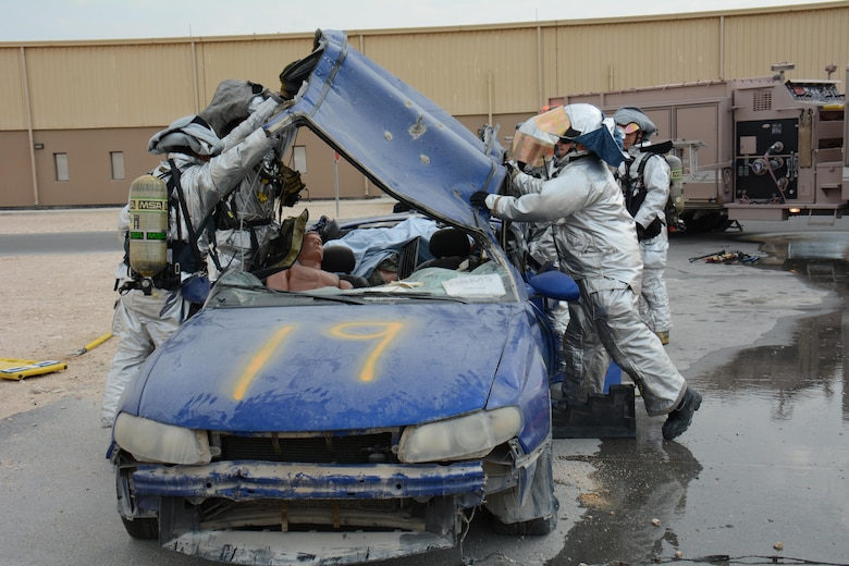 Firefighters assigned to the 379th Expeditionary Civil Engineer Squadron take the roof off of a car during an exercise at Al Udeid Air Base, Qatar Dec. 15. The exercise consisted of a car accident with eight victims; two were trapped inside the car. More than 50 first responders participated in the exercise. (U.S. Air Force photo by Tech. Sgt. James Hodgman/Released)
