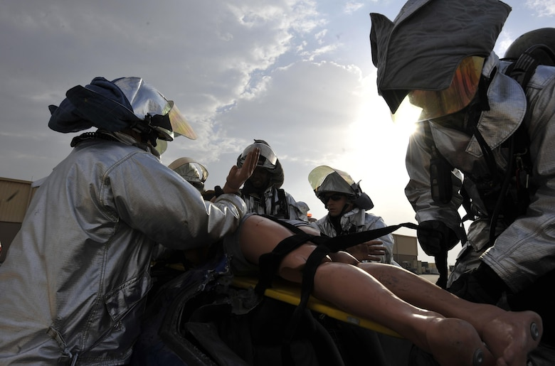 Firefighters from the 379th Expeditionary Civil Engineer Squadron, Al Udeid Air Base, Qatar pull a simulated patient from a vehicle during a mass casualty exercise at AUAB, Dec. 15. The exercise tested the emergency response capabilities of fire and medical personnel. (U.S. Air Force photo by Master Sgt. Joshua Strang)