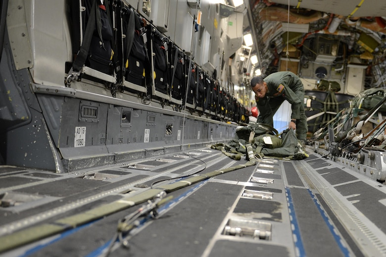 Staff Sgt. Joseph Timpson, a 10th Airlift Squadron loadmaster, checks over a parachute for an airdrop during exercise Rainier War Dec. 10, 2015, on the flightline at Joint Base Lewis-McChord, Wash. The parachute is used to pull the cargo out of the aircraft before another parachute opens up and safely drops the cargo on the drop zone. (U.S. Air Force photo/Senior Airman Divine Cox)