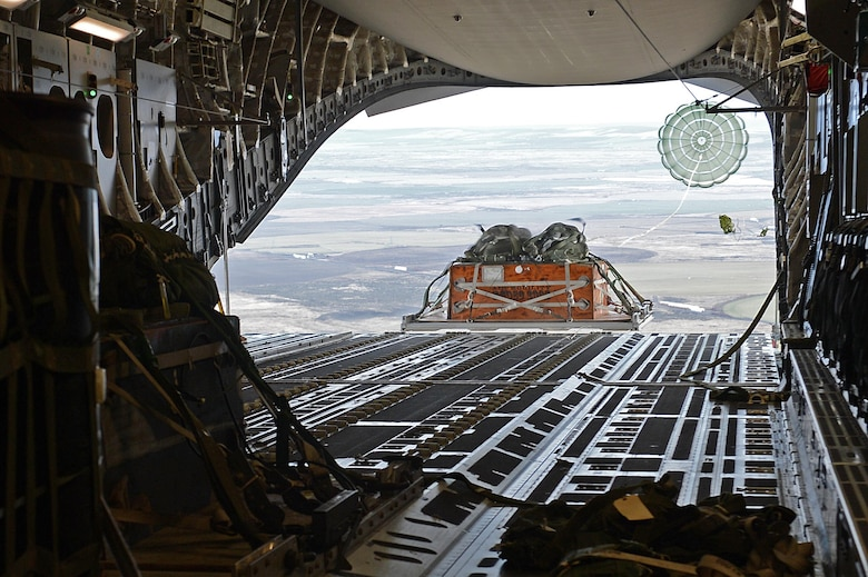 A heavy container delivery system cargo drops out the back of a C-17 Globemaster III during the exercise Rainier War Dec. 10, 2015, over the Rainier drop zone in Washington. The aircrew dropped multiple loads of cargo onto the DZ in support of the large formation exercise. (U.S. Air Force photo/Senior Airman Divine Cox)