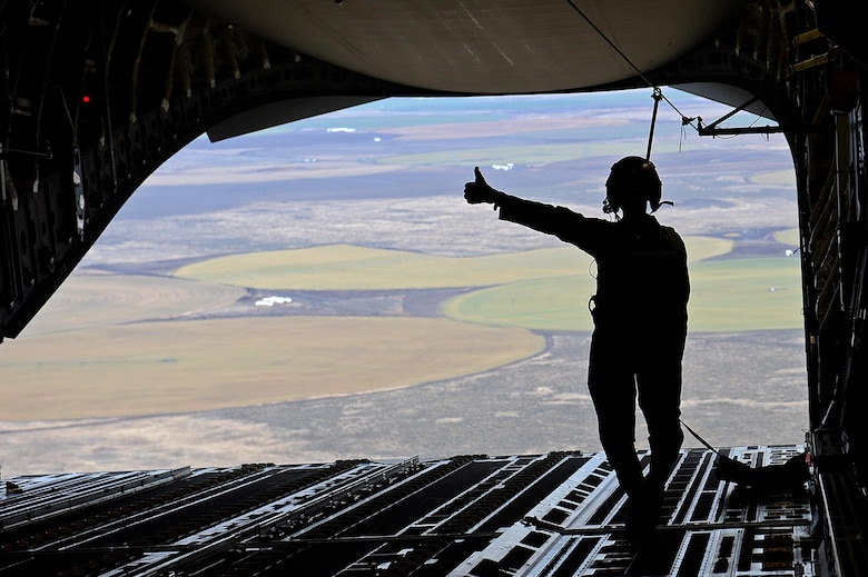 Staff Sgt. Joseph Timpson, a 10th Airlift Squadron loadmaster, gives a thumbs up after an airdrop during exercise Rainier War Dec. 10, 2015, over the Rainier drop zone in Washington. Rainier War included the large formation airdrops and a larger formation of C-17 Globemaster IIIs before heading back to Joint Base Lewis-McChord, Wash. (U.S. Air Force photo/Senior Airman Divine Cox)