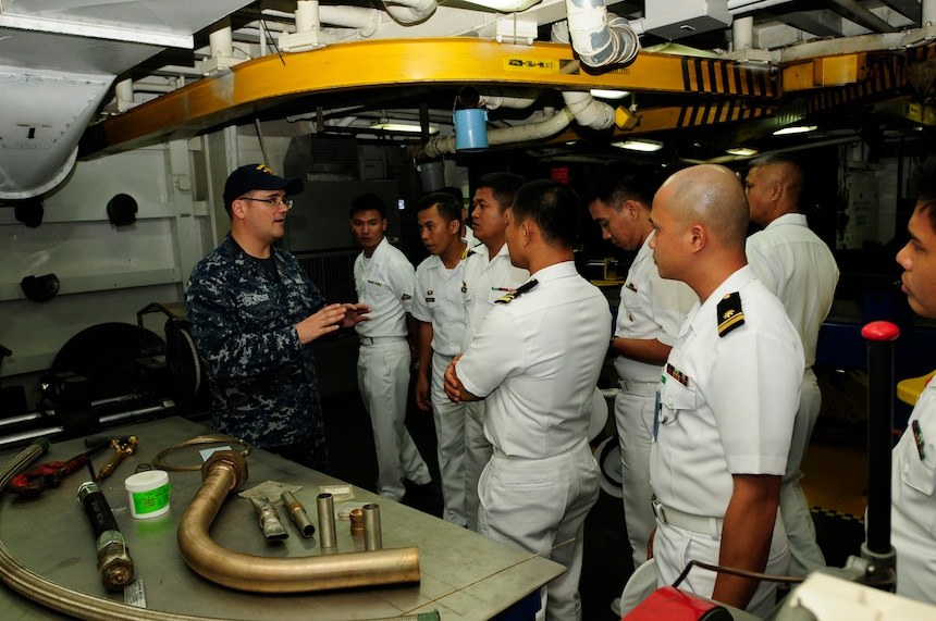 SUBIC BAY, Philippines (Dec. 11, 2015) Mass Communications Specialist 1st Class Brandon Shelander, from the submarine tender USS Emory S. Land (AS 39), gives members of the Philippine Navy a tour of Emory S. Land's repair facilities following a subject matter expert exchange held onboard. The exchange gave participants a chance to share maintenance philosophies in a relaxed environment. Emory S. Land is a forward deployed expeditionary submarine tender on an extended deployment conducting coordinated tended moorings and afloat maintenance in the U.S. 5th and 7th Fleet areas of operations. (U.S. Navy photo by Mass Communication Specialist Seaman Tiffany L. Downey/Released)