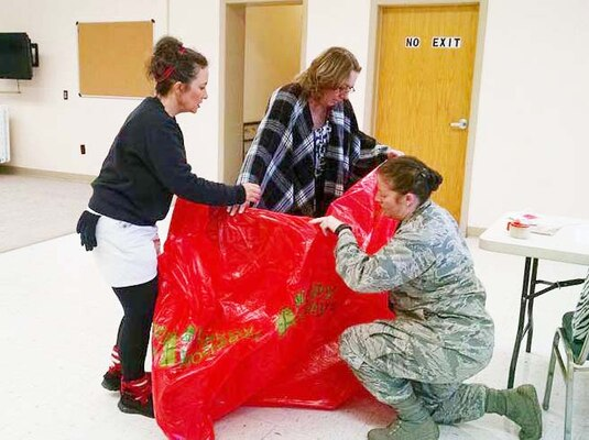 Defense Logistics Agency  Aviation employees Denise Buckley (right)  and Cathy Hopkins, along with Air Force Capt. Tiffany Sellers, bag a bicycle provided for a student receiving gifts from Bensley Elementary School's annual Angel Tree program Dec. 16, 2015.  DLA employees at Defense Supply Center Richmond, Virginia, adopted and provided gifts for 112 students in need from four local schools.
