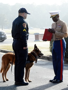 Col. James C. Carroll III (right), commanding officer, Marine Corps Logistics Base Albany, prepares to present a Meritorious Service Medal to Pablo, former military working dog, with the base's Marine Corps Police Department, during a retirement ceremony held here, Dec. 15. Pablo's former military working dog handler, civilian police officer, Cpl. Greg Madrid, received the award on behalf of the K-9.